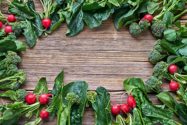 Vegetables background. radish, broccoli, spinach leaves with copy space in the middle. Premium Photo