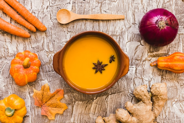 Vegetables and leaf around soup and spoon Free Photo