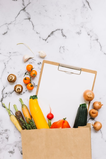 Vegetables and paper on clipboard falling from brown paper bag on marble background Free Photo