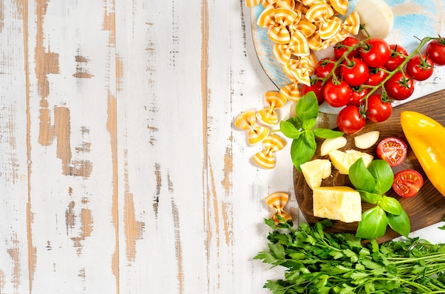 Vegetables and pasta seeing from above on white wooden table Premium Photo