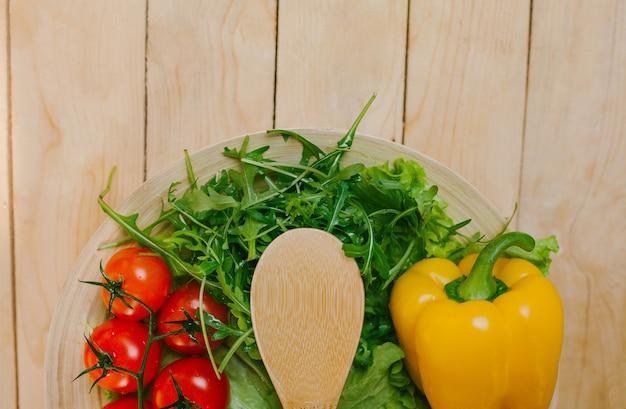 The vegetables on the plate with the wooden spoon Premium Photo