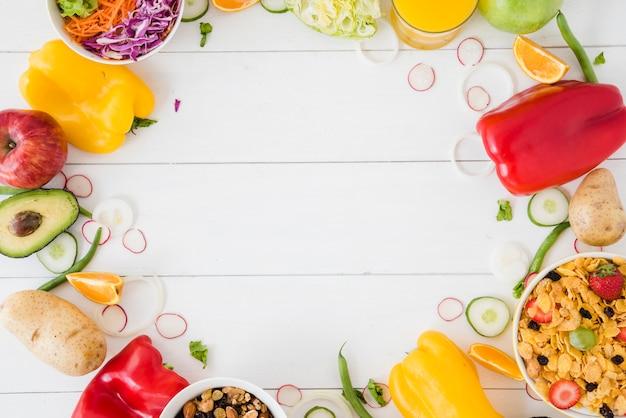 野菜;サラダ;テキストを書くためのスペースを持つ白い木製の机の上のフルーツとコーンフレークボウル 無料写真
