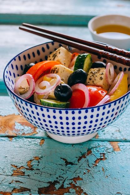 Vegetables salad and olives with chopsticks on wooden blue background Premium Photo