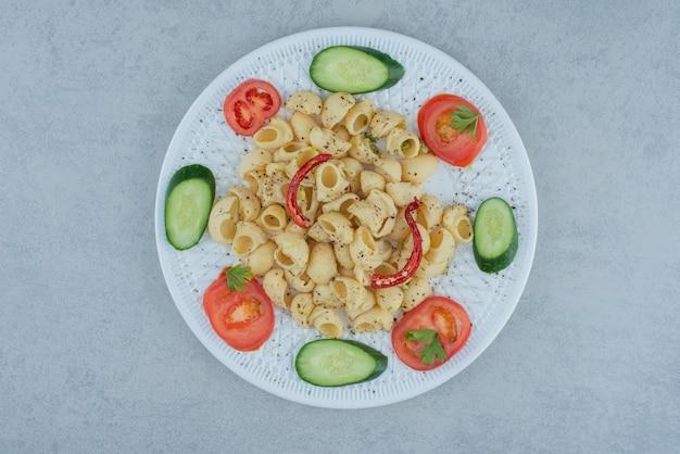 大理石の背景においしいマカロニと白いプレートの野菜サラダ 無料写真