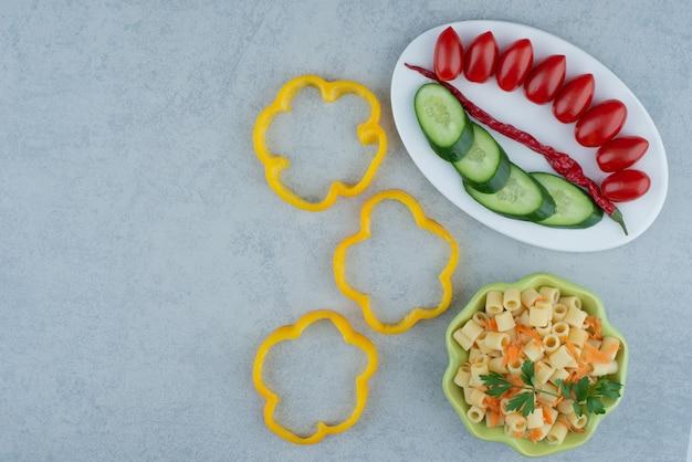 大理石の背景にマカロニと白いプレートの野菜サラダ。高品質の写真 無料写真