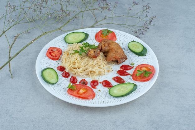 파스타와 대리석 배경에 닭고기와 흰 접시에 야채 샐러드 무료 사진