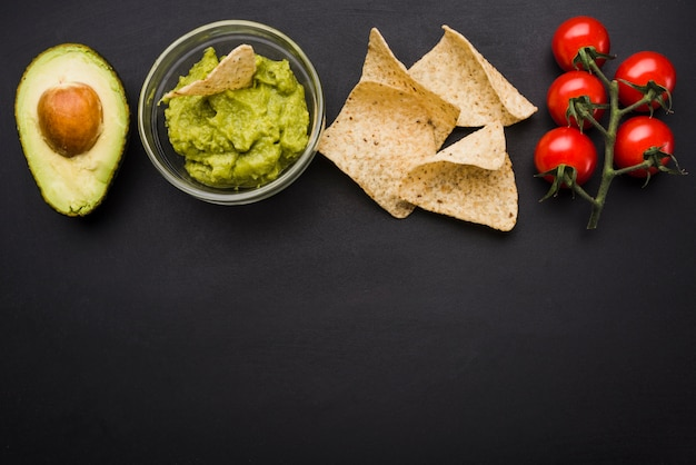 Vegetables and sauce in bowl near nachos Free Photo
