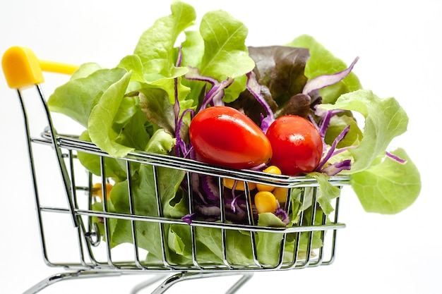 Vegetables in the shopping cart on white background Premium Photo