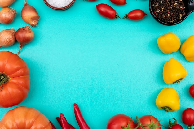 Vegetables tomatoes onion pepper top view on blue surface Free Photo