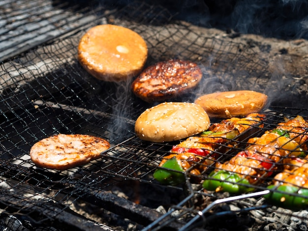 Vegetables with patties and buns grilling on rack Free Photo