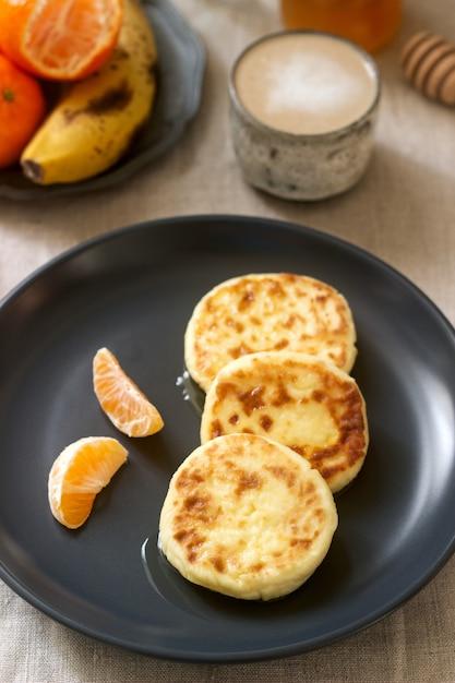 蜂蜜、フルーツ、コーヒー、ミルク入りのクォークパンケーキのベジタリアン朝食。素朴なスタイル。 Premium写真