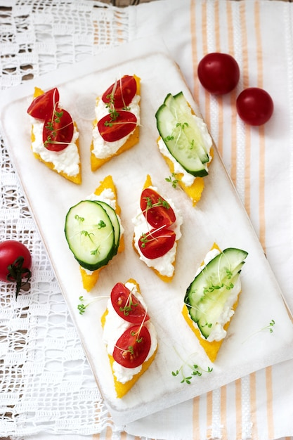 Vegetarian canapes from polenta with cheese, vegetables and cress. rustic style. Premium Photo