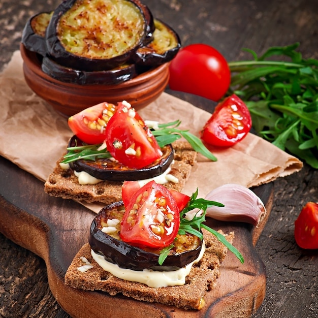 Vegetarian diet crispbread sandwiches with garlic cream cheese, roasted eggplant, arugula and cherry tomatoes on old wooden surface Free Photo