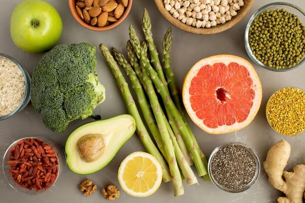 Концепция вегетарианской пищи с овощами, фруктами, орехами и пчелиной пыльцой Premium Фотографии