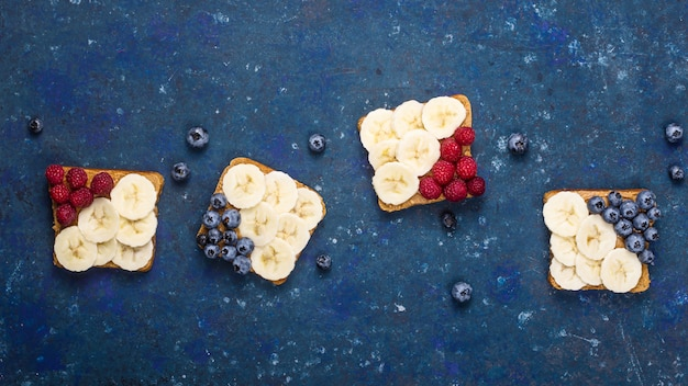 Vegetarian lunch sandwich with peanut butter, banana, raspberry and blueberry Premium Photo
