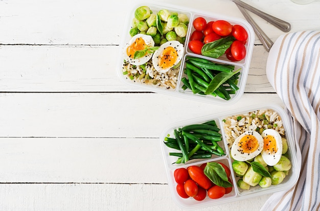 Vegetarian meal prep containers with eggs, brussel sprouts, green beans and tomato. dinner in lunch box. top view. flat lay Free Photo
