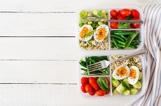 Vegetarian meal prep containers with eggs, brussel sprouts, green beans and tomato. Premium Photo