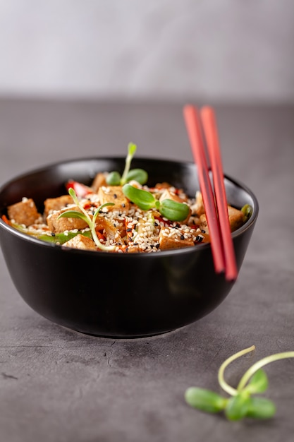 Vegetarian noodles with tofu cheese and vegetables in a black ceramic plate. Premium Photo
