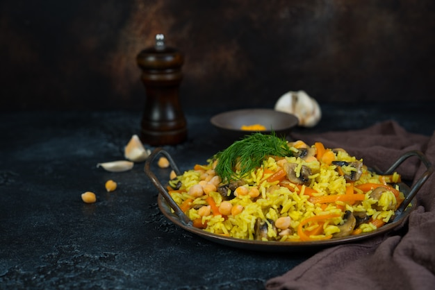 Vegetarian pilaf with mushrooms, vegetables and chickpeas on the right on a black wall. horizontal photo with copy space. Premium Photo