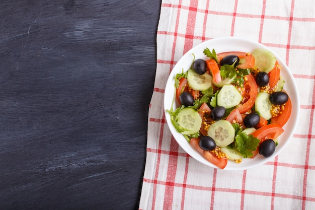 Vegetarian salad of tomatoes, cucumbers, parsley, olives and mustard on linen tablecloth. Premium Photo