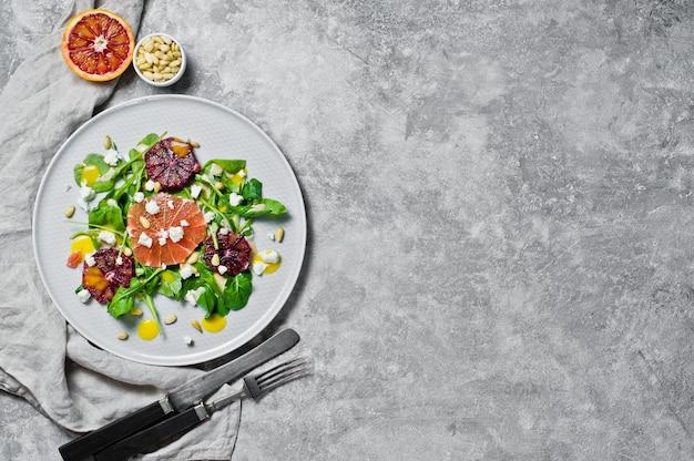 Vegetarian salad with arugula, grapefruit, red oranges, nuts and tofu cheese. Premium Photo