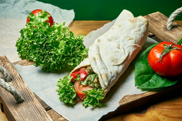 Vegetarian shawarma roll in pita with lettuce, vegetables, and tomato. tasty, wholesome and green food. vegan street food Premium Photo