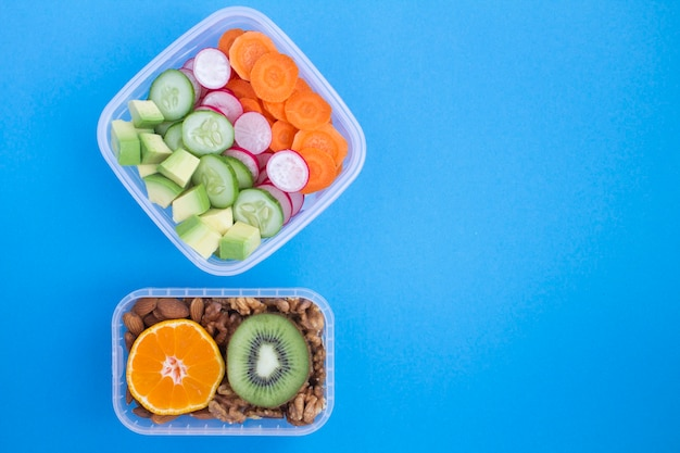Vegetarian snack or lunch  in the two boxes on the blue Premium Photo