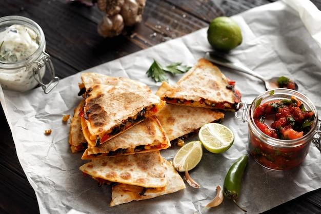 Vegetarian snacks quesadilla vegetables cheese dark wooden table Premium Photo