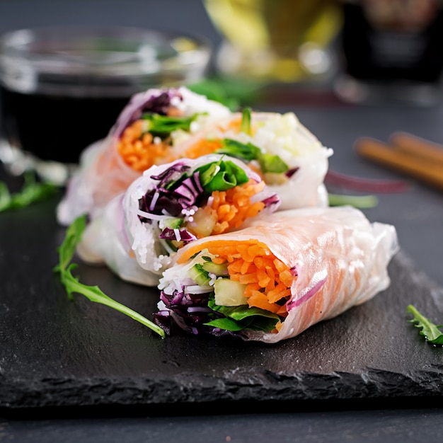 Vegetarian vietnamese spring rolls with spicy sauce, carrot, cucumber, red cabbage and rice noodle. Premium Photo