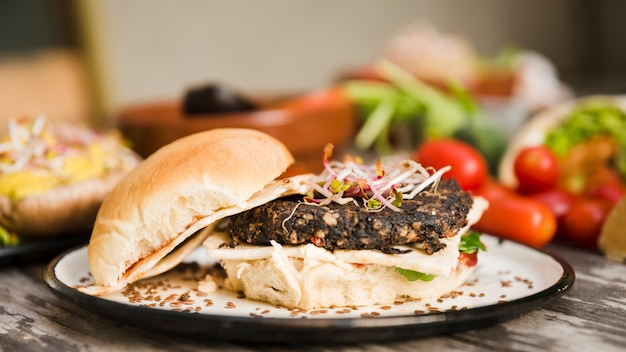 Veggie quinoa burger with sprouts and flax seeds on white plate Free Photo