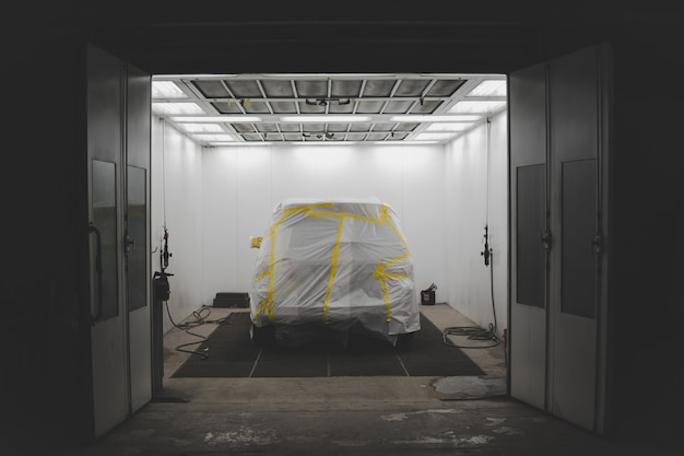 Vehicle covered with a white sheet and yellow tape in a car service garage Free Photo