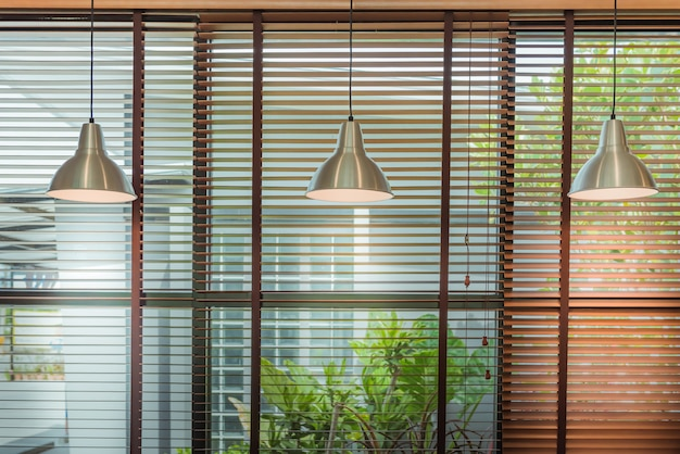 Venetian blinds by the window or blinds window and ceiling lamp beam, blinds window decoration concept. Premium Photo