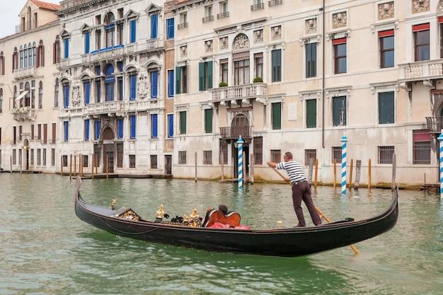 イタリア、ヴェネツィアの緑の運河の水を介してゴンドラをパントするヴェネツィアのゴンドラ Premium写真