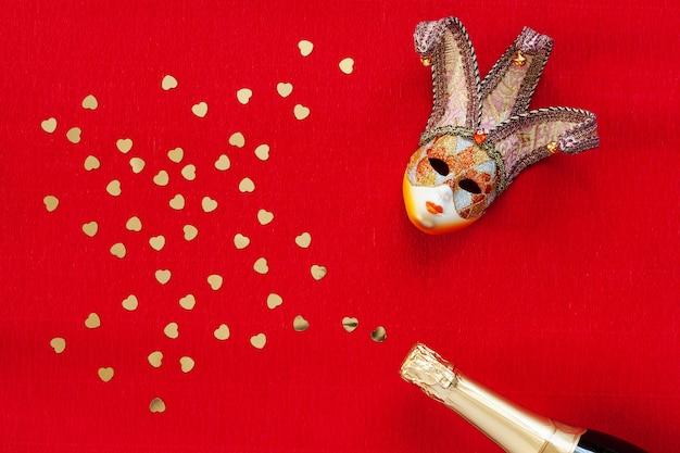 Venetian mask, champagne bottle with heart gold confetti. top view, close up on red background Premium Photo