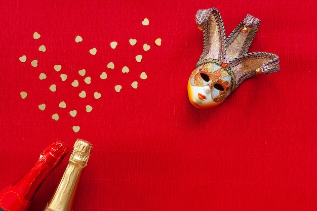Venetian mask, two champagne bottles with heart gold confetti. top view, close up on red background Premium Photo