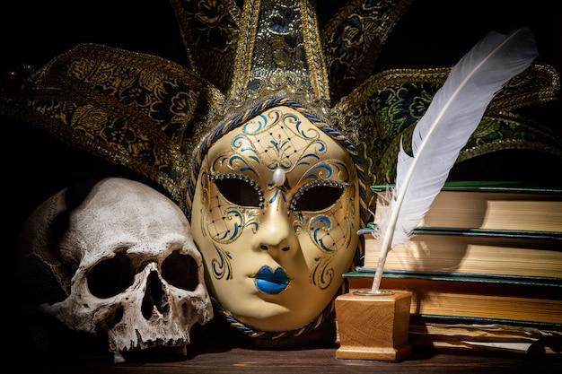 古いインクつぼ、羽、羽、本、木製のテーブルの上の頭蓋骨とベネチアンマスク。 Premium写真