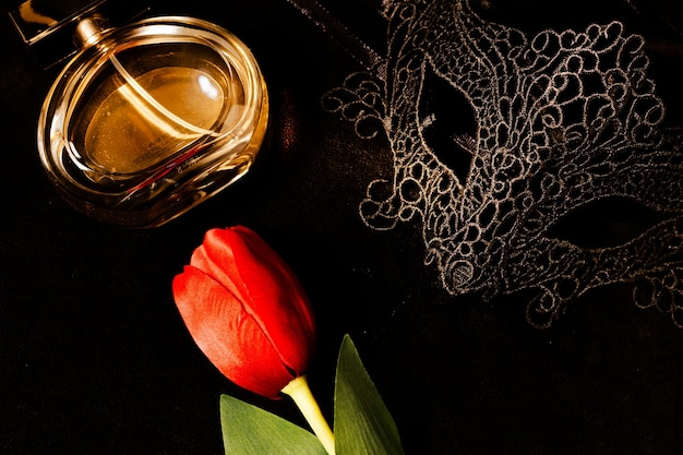 Venetian mask with a red tulip and perfume in a dark, suggestively lit environment. mysterious love concept, san valentin day. Premium Photo