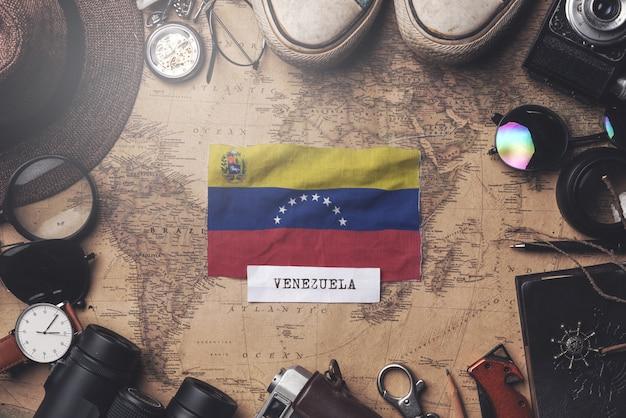 Флаг венесуэлы между аксессуарами путешественника на старой винтажной карте. верхний выстрел Premium Фотографии