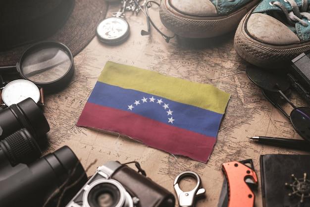 Флаг венесуэлы между аксессуарами путешественника на старой винтажной карте. концепция туристического направления. Premium Фотографии