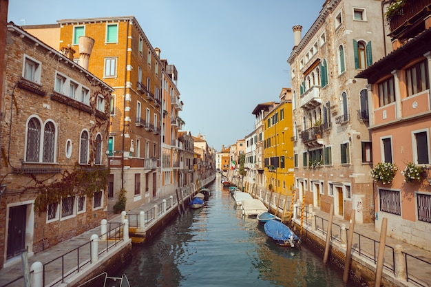 ヴェネツィア、素晴らしい運河とゴンドラのある海の美しいロマンチックなイタリアの街。ベネチアの狭い運河の眺め。ヴェネツィアはヨーロッパの人気のある観光地です。 Premium写真