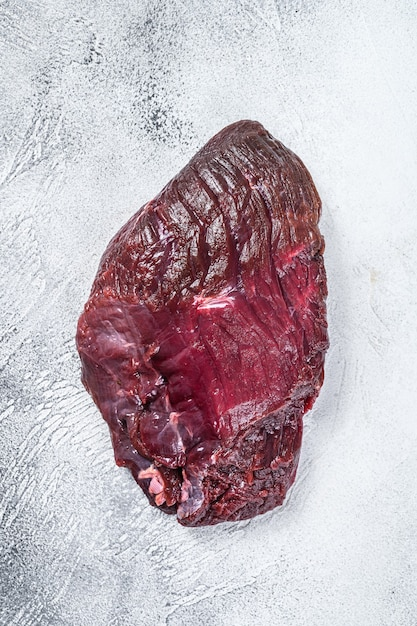 Venison raw deer meat on a table. white table. top view. Premium Photo