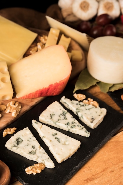 Verity of tasty cheeses and walnut on wooden surface Free Photo