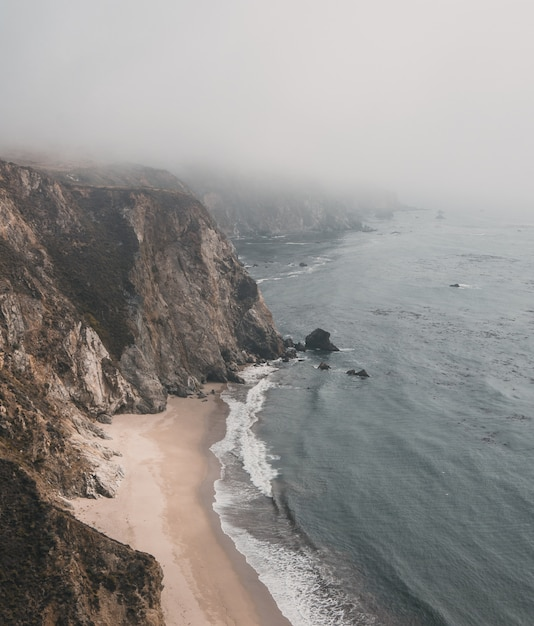 Vertical aerial shot of a cliff by the sea with sandy shore under a foggy sky Free Photo