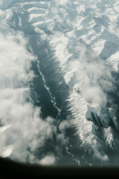 Vertical aerial shot of the mountains covered with snow Free Photo