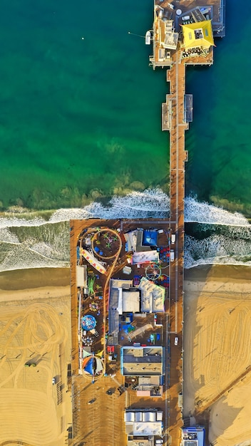 Vertical aerial shot of a park with different kinds of rides at the beach Free Photo
