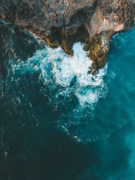 Vertical aerial shot of sea waves hitting the cliff Free Photo