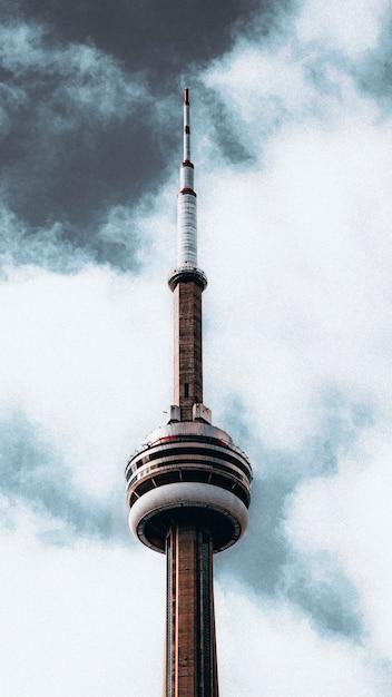 暗い曇りの灰色の空の下でラジオ塔の上部の垂直方向の美しいショット 無料写真