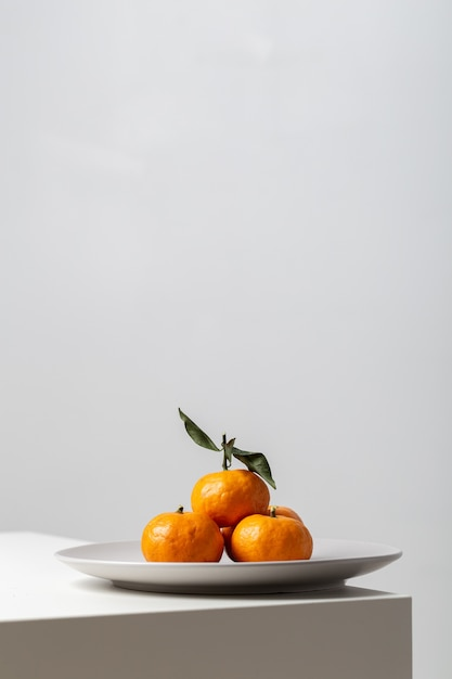 Vertical closeup of mandarines on a plate on the table under the lights against a white background Free Photo