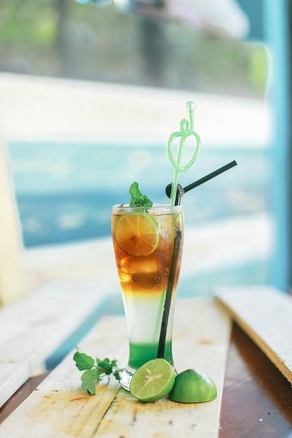 Вертикальный крупный план вкусного холодного коктейля на столе с лаймами под огнями Бесплатные Фотографии