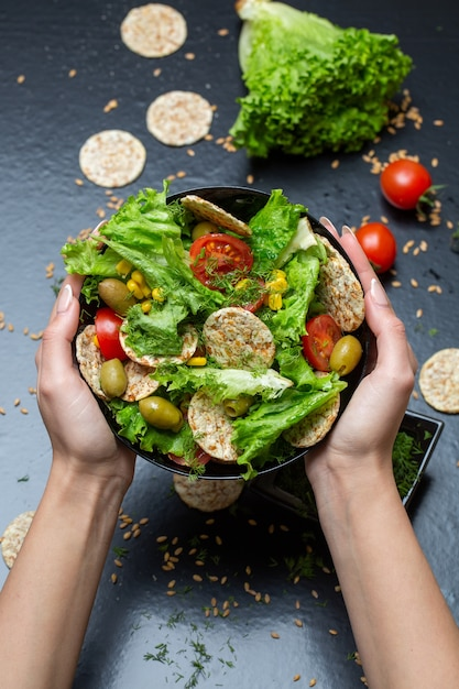 Vertical closeup of a person holding a bowl of salad with crackers and vegetables under the lights Free Photo